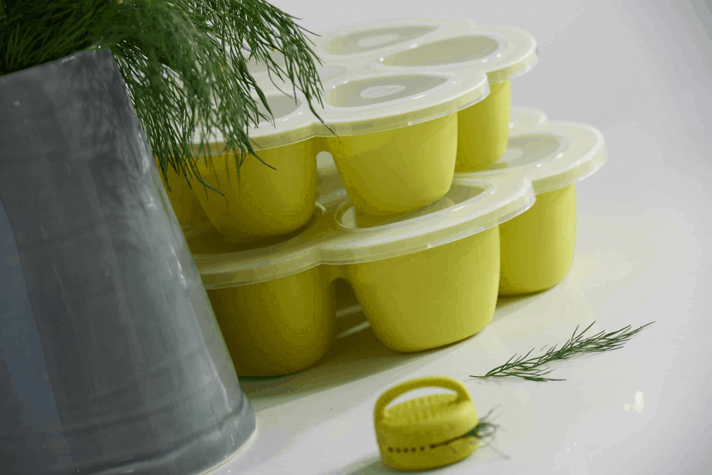 Béaba Multiportions™ Silicone Tray in Neon with plant in front