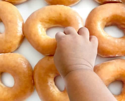 Baby reaching for donuts