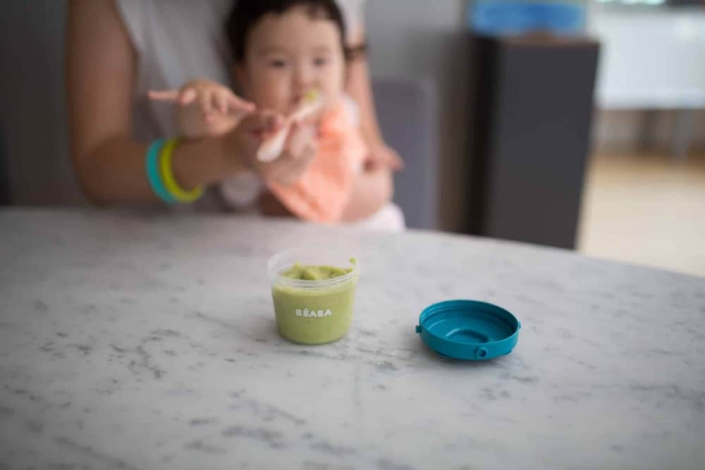 Baby being fed puree with Beaba silicone spoons out of clip container