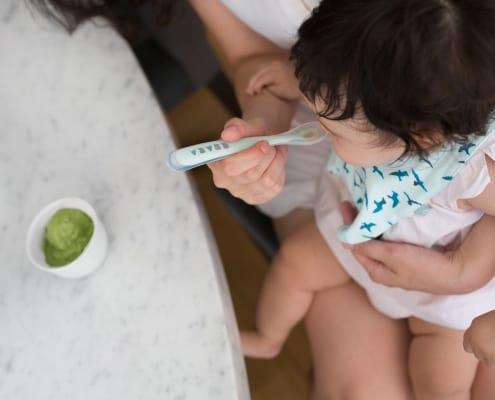 mom spoon feeding baby puree