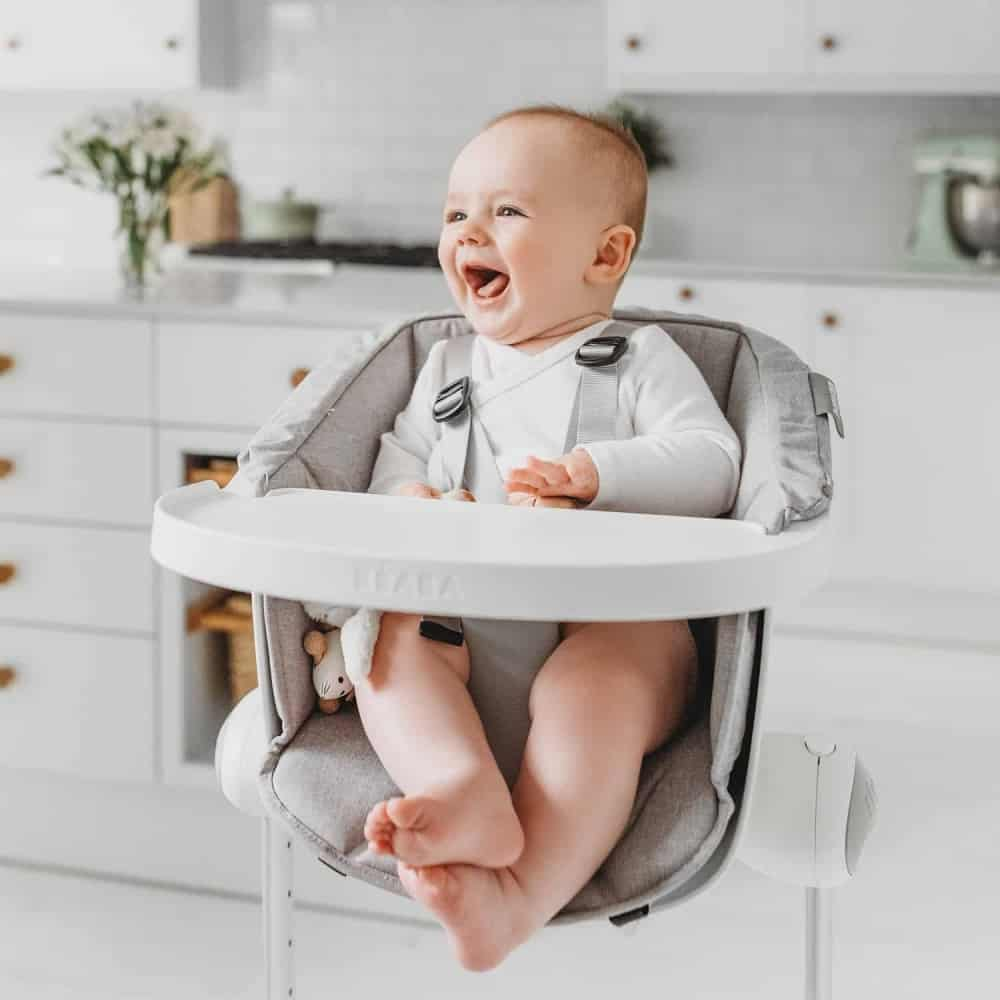 Baby smiling and sitting in BEABA Up & Down High Chair