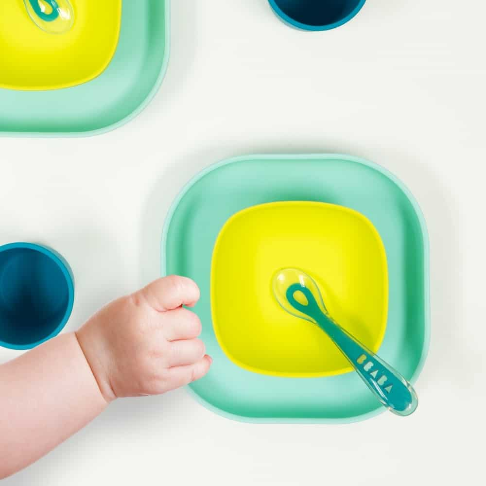 Baby hand reaching for silicone suciton meal set peacock