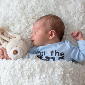 baby with acne lying on fluffy white bed holding a stuffed toy rabbit