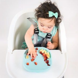 Toddler picking fruit from silicone suction meal set pastel
