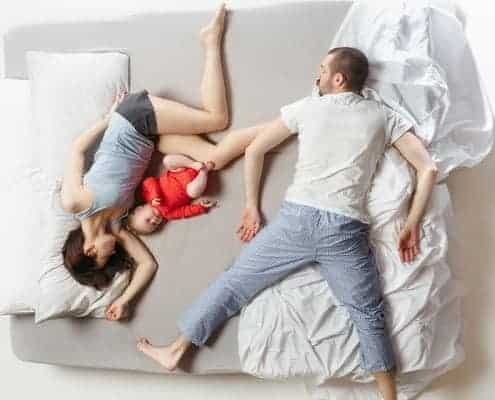 Family sleeping on bed