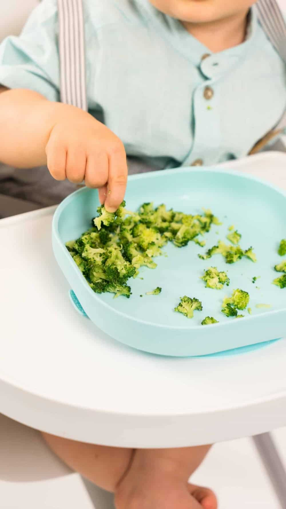 Toddler Grabbing Broccoli from Silicone Plate Rain in High Chair