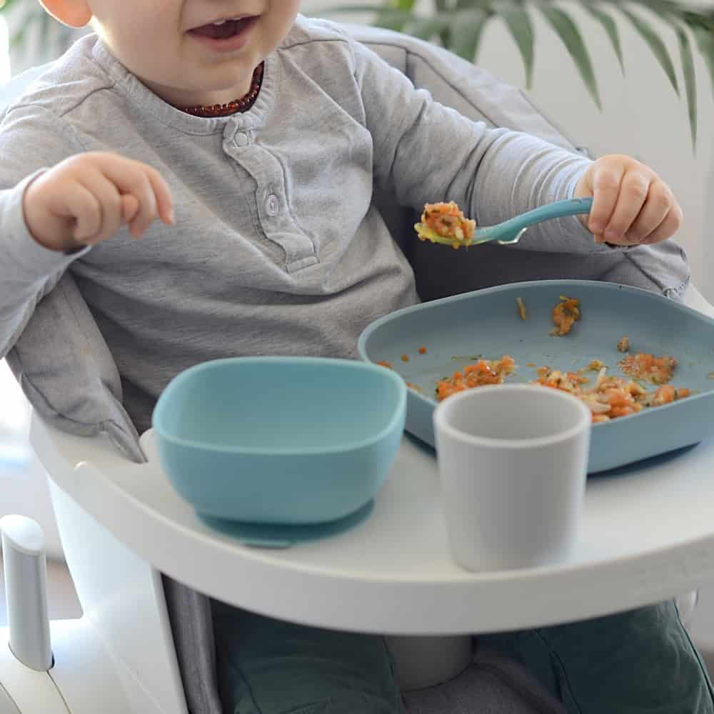 Baby eating with Beaba Silicone Suction meal set in rain with puree
