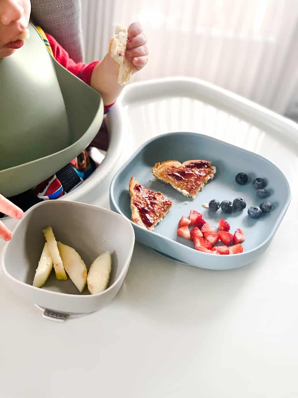 Toddler Eating Fruit from Silicone Suction Meal Set in Rain