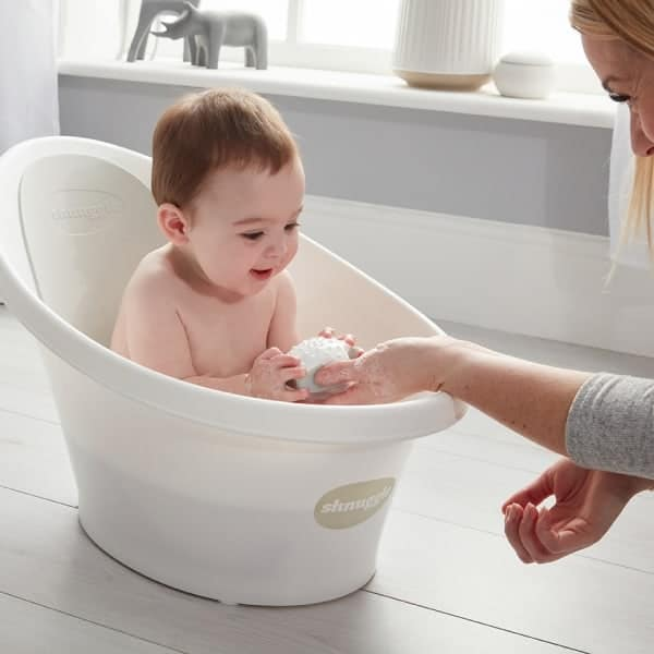 Baby playing in Beaba by Shnuggle Baby bath in grey