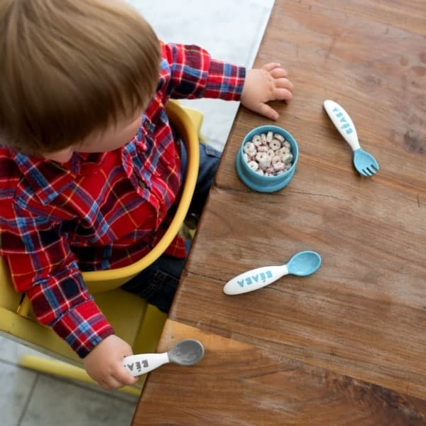 Toddler sitting at Table Using Toddler's Self Feeding Cutlery Set Rain and Cloud