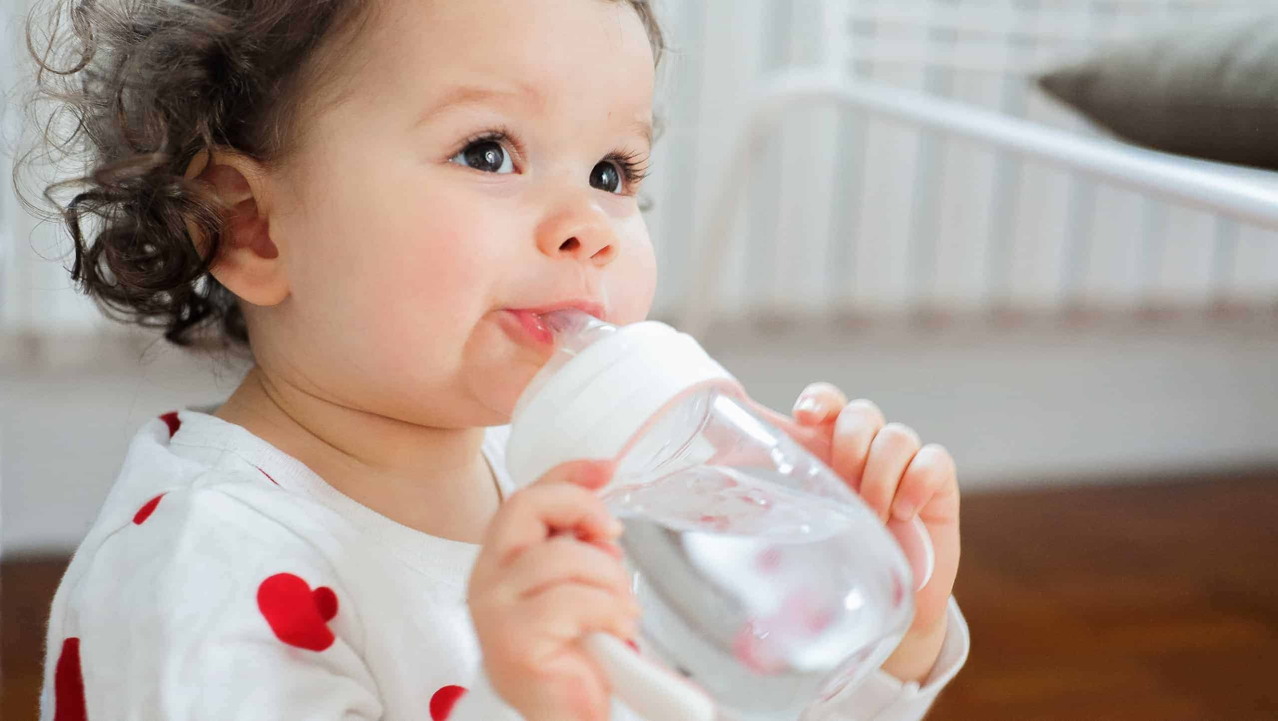 Baby holding BEABA 2-in-1 Training Cup