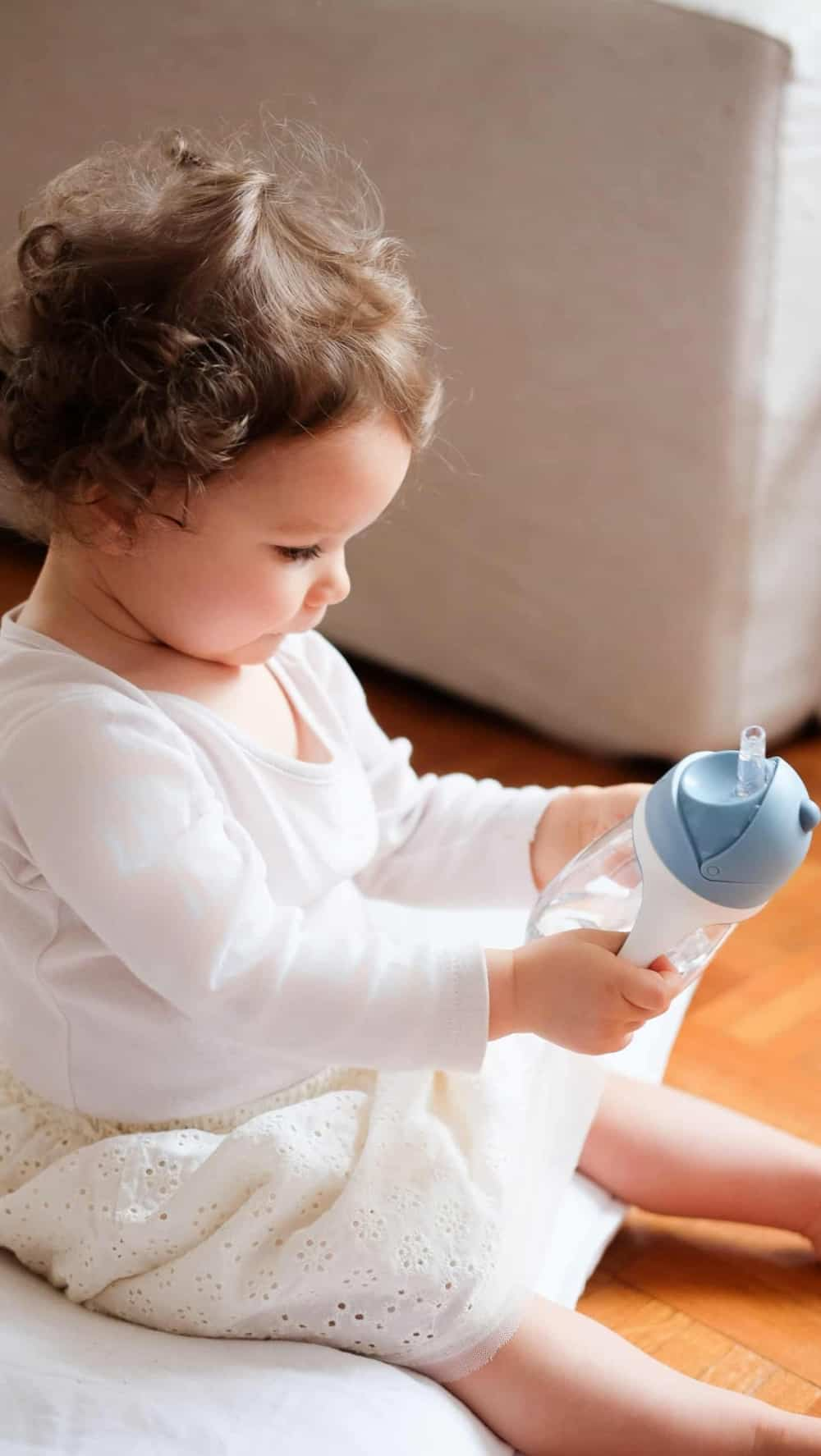 Baby holding Beaba Straw Cup Rain