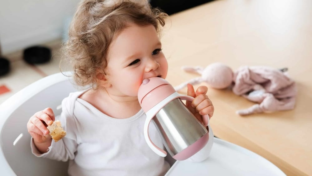 baby drinking from straw cup