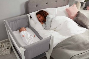 Mom Looking At Baby In Beaba by Shnuggle Air Bedside Sleeper Infant Crib
