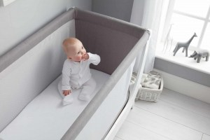 Baby lounging in BEABA by Shnuggle Air Cot Conversion Kit