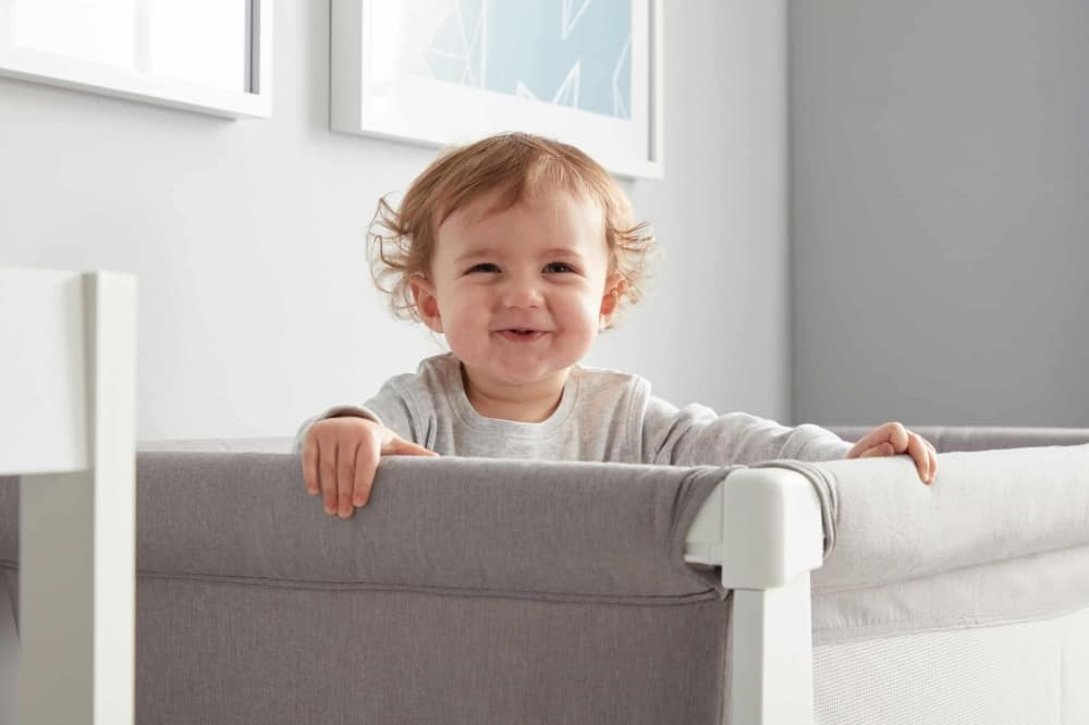 Baby smiling while in BEABA by Shnuggle Air Cot Conversion Kit