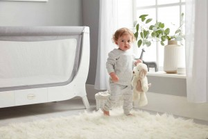 Baby holding stuffed animal next to Beaba by Shnuggle Air Full Size Crib