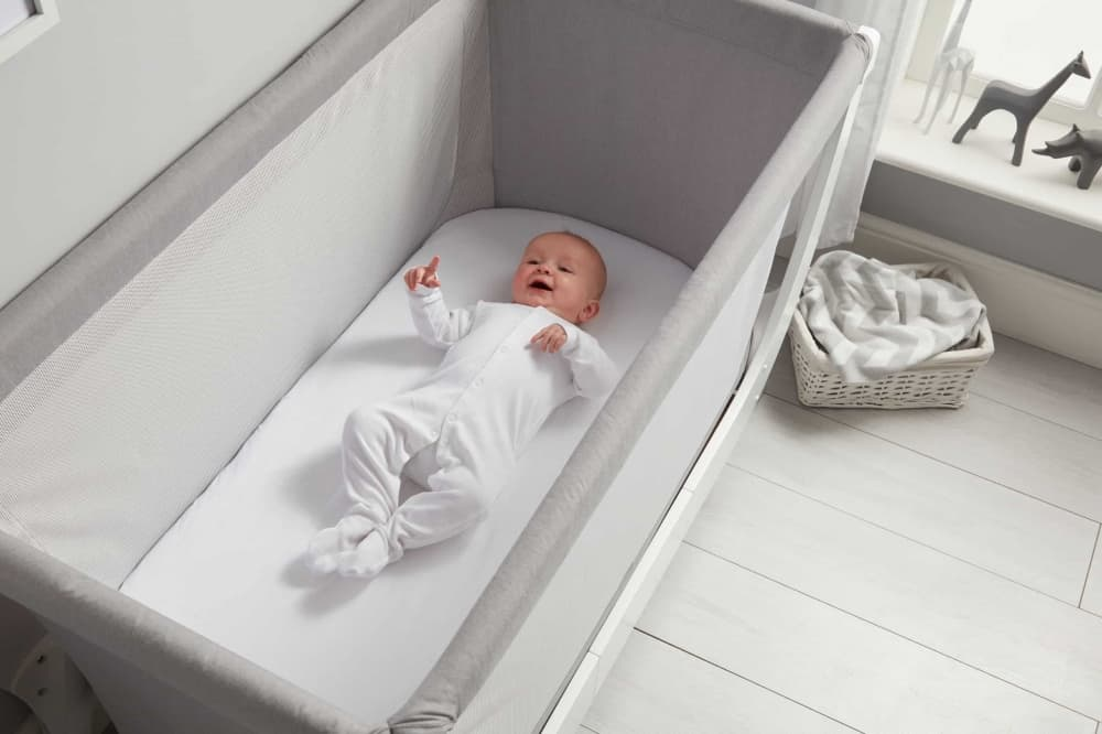 Baby laying in BEABA by Shnuggle Air Folding Cot Mattress