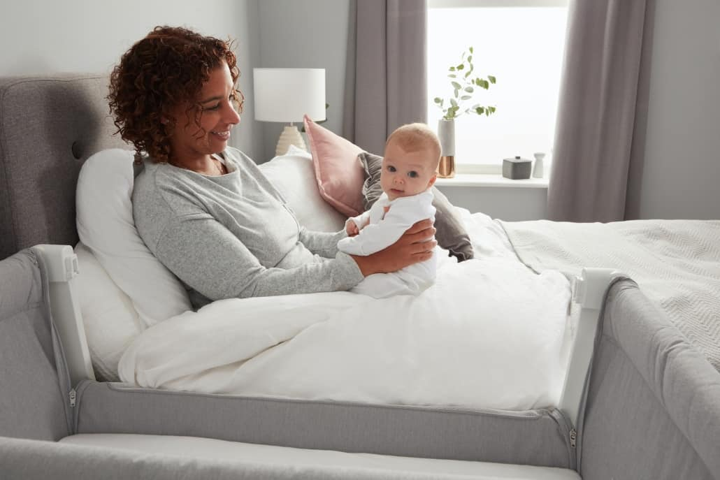 Mom Holding Baby In Bed