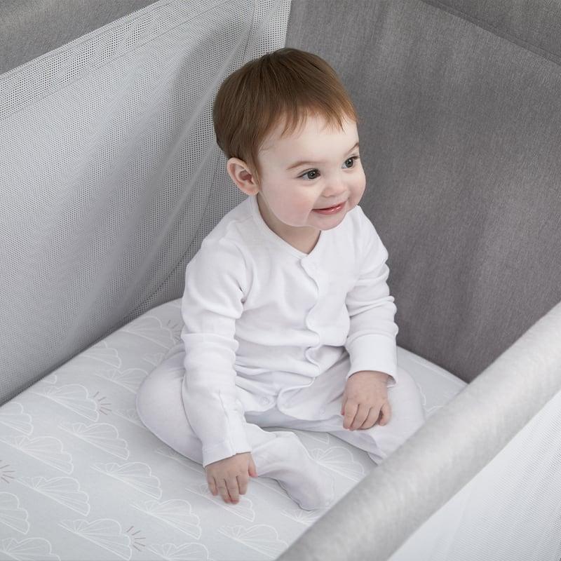 Baby sitting in Beaba by Shnuggle Air Cot Sheets close up