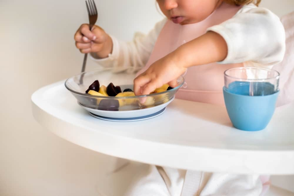toddler eating from glass meal set