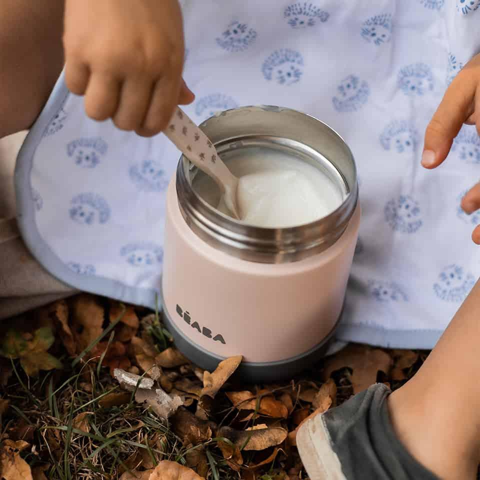 Baby girl scooping yogurt out of stainless steel jar