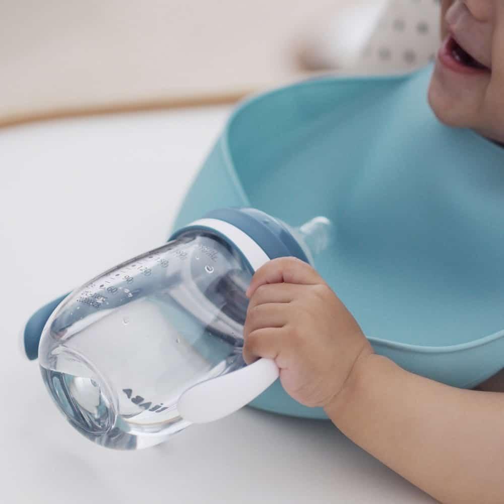 Child Wearing Beaba silicone bib rain drinking from beaba sippy cup