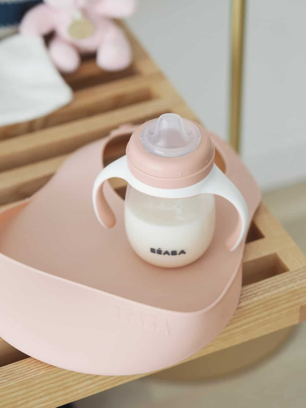 Silicone Bib on Table Next to Sippy Cup